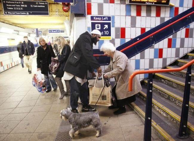 A man who missed his train helping this older lady with her bags