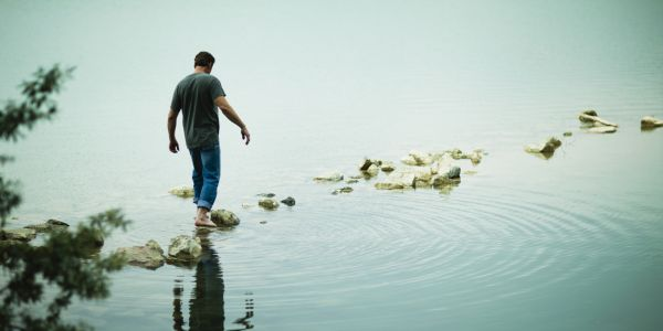 Man walking on stepping stones over river - State vs. Trait Mindfulness measuring mindfulness