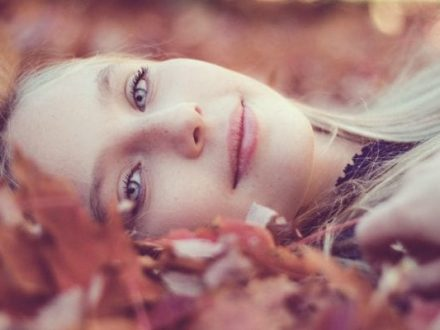 Woman Lying Down On Autumn Leaves
