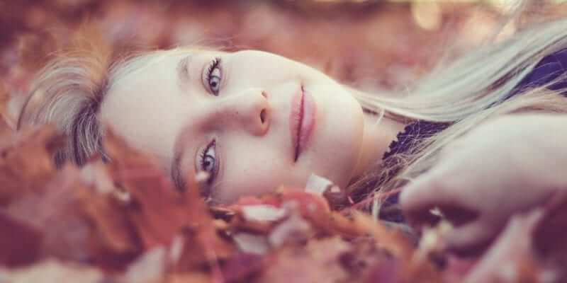 Woman Lying Down On Autumn Leaves - What is Self-Acceptance?