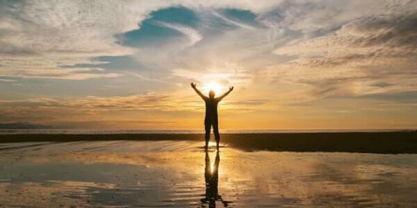 man with the arms in the air in front of ocean - self-acceptance